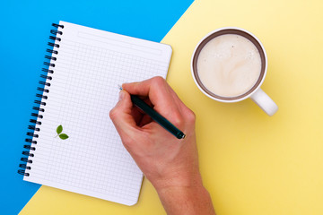 Top view on writing men hand in blank notebook and near cup of coffee, separated on yellow and blue paper background.