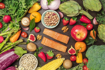 Overhead photo of fresh vegetables, legumes, fruits, and fish, healthy diet