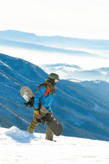 Young snowboarder walking at the top of a mountain with snowboard in his hand