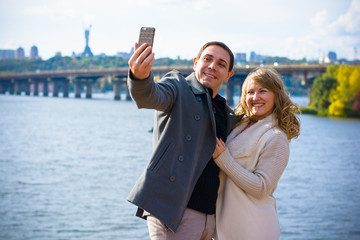 Happy traveling middle age couple making selfie city background , sunny spring or autumn colors, romantic mood. Stylish pretty people. Happy laughing emotional faces.
