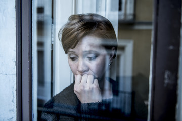 dramatic close up portrait of young beautiful woman thinking and  feeling sad suffering depression at home window looking depressed