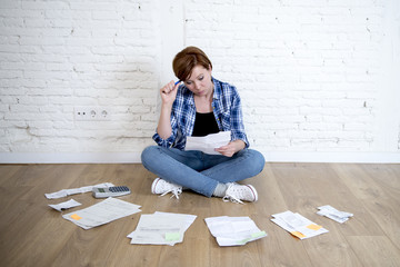woman at living room floor with calculator and bank and bills paperwork and documents doing domestic financial accounting