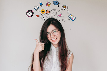 Head shot of Young cute asian student wearing glasses and smiling with thumb up with education and learning illustration doodles background -Education and graduation Concept.