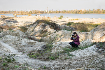 Woman with a camera photographing sitting down in the sand