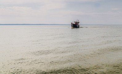 Fishing trawler in the sea bay. Quiet water surface