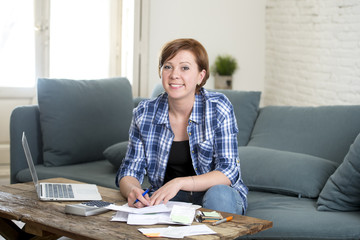 happy woman banking and accounting home monthly and credit card expenses with computer laptop doing paperwork