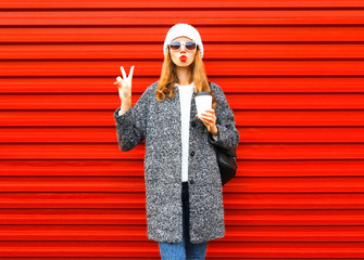Fashion pretty woman with coffee cup in coat posing on red background Wall mural