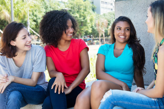 Group of pretty female young adults talking outdoors