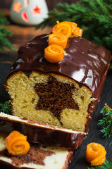 Christmas chocolate cake with orange candied peel on the table decorated with candles and green fir-tree brunches.