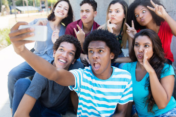 Group of young adults making funny selfie shots with phone