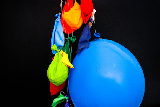 Some burst, deflated balloons and one inflated balloon hanging on threads.