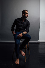 Portrait handsome fashionable man in a black shirt sits on a chair in a photo studio loft.