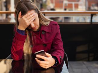 Worried teenager girl looking at her smart phone