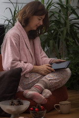 Mature woman browsing the Internet at home in preparation for winter holidays