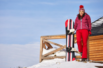 winter, leisure, sport and people concept - happy young woman in red hat outdoors