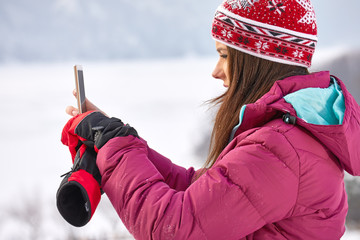 Young woman taking the photo on a background of snow-covered winter forest. Snowy weather.
