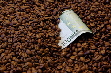 100 Euro banknote in the roasted coffee beans