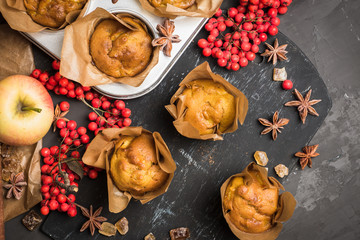 Muffins with pumpkin and apples on the rustic background with autumn decorations. Selective focus.