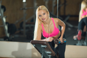 young beautiful blond girl is engaged in sports training with dumbbells in the gym
