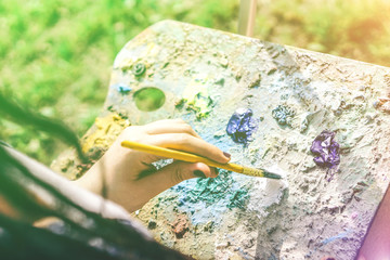 Young artist painting in a park outdoor - Close up of painter with dreadlocks hairstyle working on her art in a colorful garden - Concept of people expressing arts - Focus on hand paint