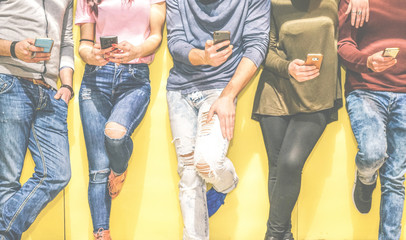 Group of young friends leaning on a wall using mobile phones - Multiracial people connecting on social network with smart phone - Young generation addicted to new technology concept