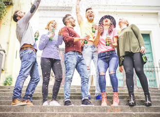 Group of happy friends celebrating together throwing up confetti and drinking beers - Young people having a party on stairs of an urban area in the city outdoor - Friendship, fun, lifestyle concept