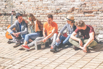 Group of friends enjoying together a sunny day outdoor listening music with a vintage stereo - Happy young people having fun sitting outside university - Concept of friendship, lifestyle and music