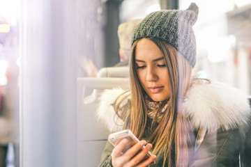 Young woman using her smart phone while sitting in a bus - Pretty girl connecting on her social network with her mobile phone - Concept of youth people addiction to new technology