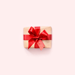 Gift box with red ribbon on pink background