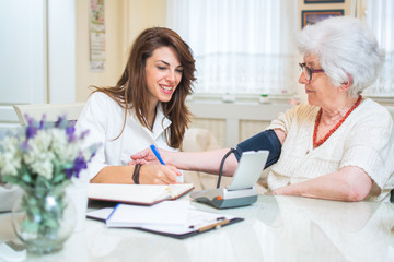 Nurse with clipboard writing results of blood pressure measurement of female senior patient.