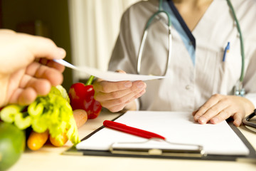 Vegetable diet nutrition and medication concept. Nutritionist is giving prescription and offers healthy vegetables diet.