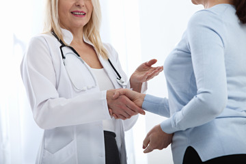 Healthcare and medical concept - doctor with patient in hospital. Handshake.