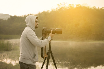Handsome young professional photographer taking photos,