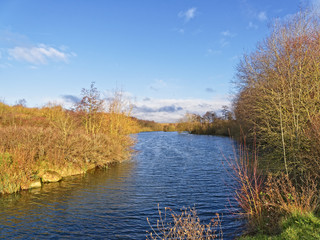 The narrow entrance to a small lake winds between trees and shrubs dressed in autumn colours. The clear blue sky is reflected in the rippled surface of the lake.