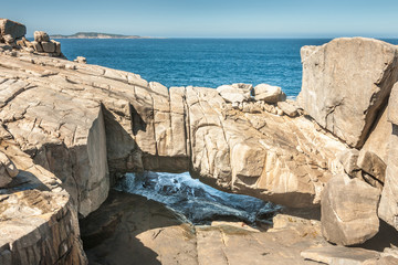 Albany WA, Australia - November 23, 2009: Beige huge Gapanda Bridge Rock In Torndirrup National Park with blue ocean under and above on coastline of Great Australian Bight. Small stroke of blue sky.