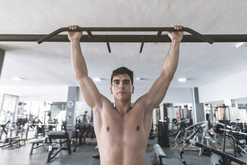 Young shirtless man training chins up in gym
