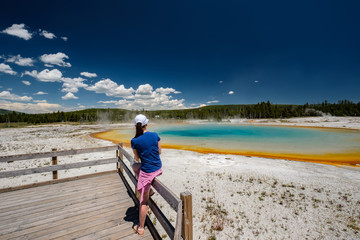 Woman tourist overlooking thermal spring in Yellowstone