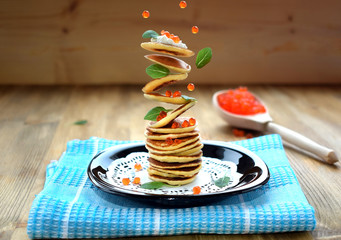 Flying pancakes, red caviar and basil leaves. Levitating food on a wooden background