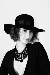 Black and white portrait, young fashion model, face with hat, accessories on naked body, jaket, bw, isolate