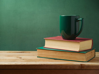 Green cup of coffee on stack of books