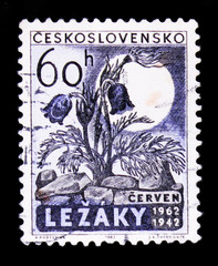 MOSCOW, RUSSIA - JUNE 20, 2017: A stamp printed in Czechoslovakia shows flower and moon, devoted to 20 years anniv of Lezaky village razed by Nazy forces, circa 1962