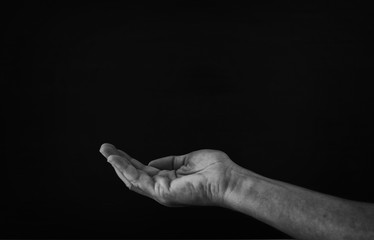 black and white image of open male hand begging for help.