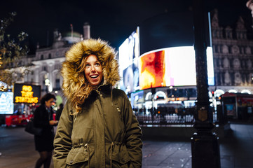 Young woman enjoying Christmas lights in Picadilly Circus, London