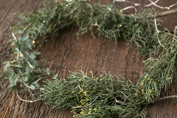 embellishment, nature elements, illumination concept. fresh green branches of cypress and other conifer trees, that are placed on the table, and among them there are tiny twinkle lights