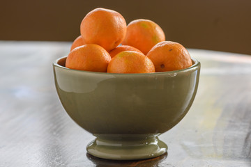 Green bowl of mandarin oranges on wood table with natural light