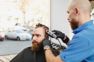 Male professional hairdresser serving client by clipper. Ginger handsome brutal stylish young man with thick big beard and short hair getting trendy haircut in black cape. Light white barber shop room
