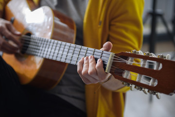 Close up of male arm playing guitar skillfully. Focus on man fingers touching the strings while doing accord