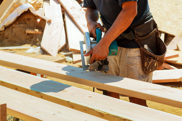 Carpenter using circular saw for cutting wooden boards. Construction details of male worker or handy man