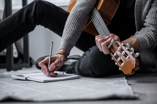 Low angle close up of male hand writing into the notebook by pencil. Young man is sitting on floor and holding guitar