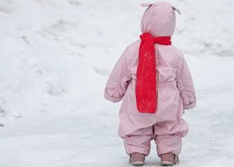 Small child in pink overalls with bunny ears lies and the bright scarf is walking on the snow in winter. Full body portrait of kid from behind against snow cover background.